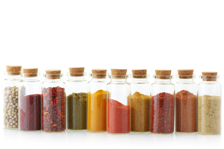 Assorted ground spices in bottles isolated on white background.