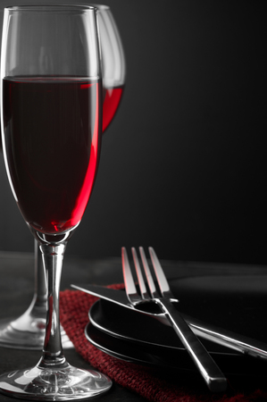Two glass of red wine, plates and silverware on dark wooden table. photo