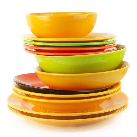 Stack of colorful ceramic dishware isolated on white background. photo