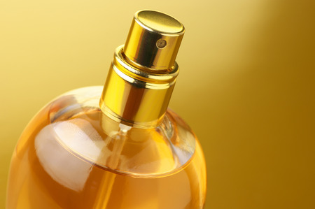 Bottle of woman perfume close-up on gold background. Imagens