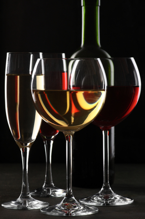 glass of wine: Various glasses of red and white wine with abstract pattern and bottle on black wooden background.