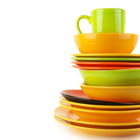 Stack of colorful ceramic dishware close-up on white background with copy space. photo
