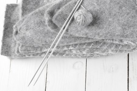 weave ball: Stack of gray warm fluffy socks with knit needles and ball on white wood.