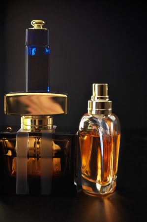 Various bottles of woman perfume on dark background. photo
