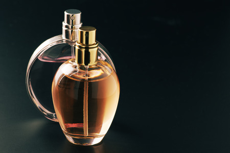 Two bottles of woman perfume on dark background with copy space. Stockfoto