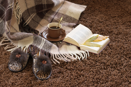 Woolen plaid, coffee cup, book and slippers on shaggy carpet. Focus on slippers. photo