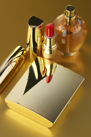 Cosmetic set. Gold powder, lipsticks and perfume on golden background. photo