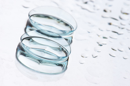 Close-up of two wet soft contact lenses with reflection on light background with drops and copy space. Shallow DOF.
