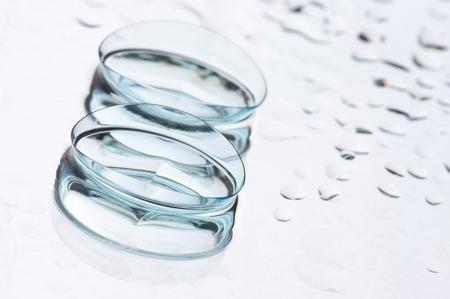 lentes de contacto: Primer plano de dos lentes de contacto blandas húmedas con la reflexión sobre fondo claro con gotas y copia espacio. DOF superficial. Foto de archivo