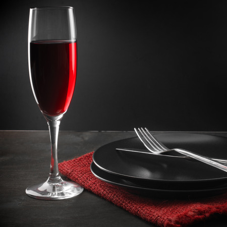 Glass of red wine, plates, silverware and napkin on dark wooden table. photo