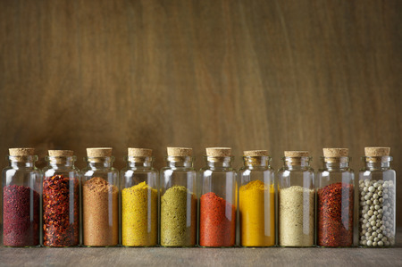 chili powder: Assorted ground spices in bottles on wooden background. Stock Photo