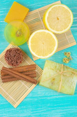 Various natural soaps, lemon and cinnamon on aquamarine wooden background. Top view point. photo
