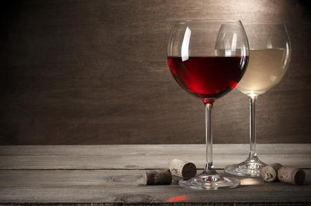 Glazen rode en witte wijn met kurken op rustieke houten achtergrond met kopie ruimte.