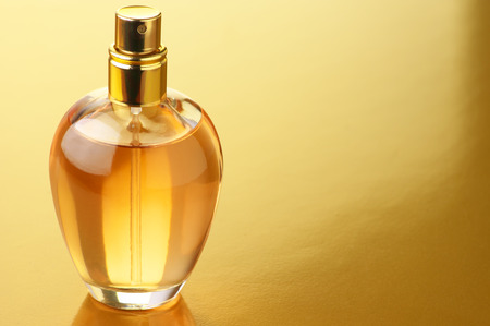 Bottle of woman perfume on gold background. photo