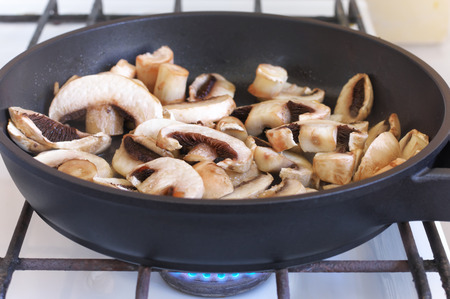 Chopped mushrooms frying in pan on stove. photo