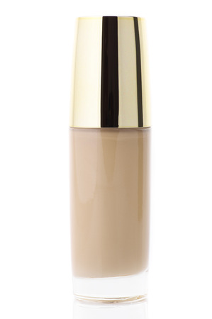 gold facial: Glass bottle of cosmetic liquid foundation isolated on white background.