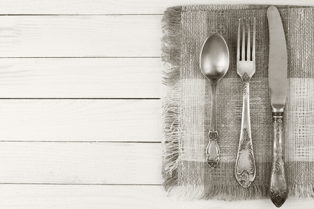 Cutlery set: vintage knife, fork and spoon on white wooden background. Toned image, sepia. photo