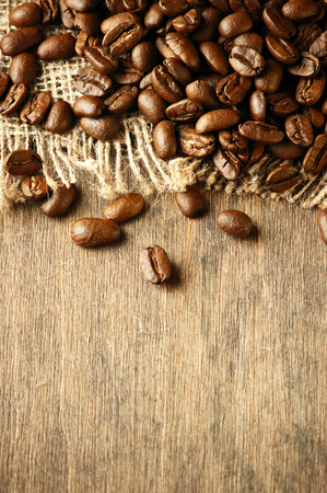 Roasted coffee beans on textured wood. photo
