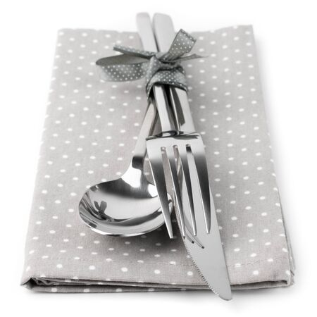 Cutlery set: spoon, fork and knife on gray napkin isolated on white background. photo