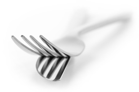 prongs: Close-up of fork and knife isolated on white background. Soft focus, shallow DOF. Focus on top of prongs.