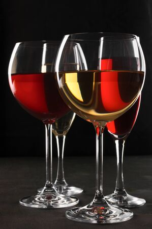 Various glasses of red and white wine with abstract pattern on black wooden background. photo