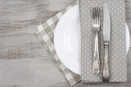 テーブルの設定: 白いプレート、ヴィンテージのフォークおよびナイフ素朴な木製のテーブルにナプキンを。トップ ビュー ポイント。