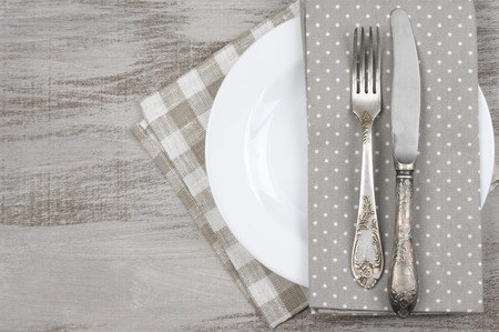 wooden table top view: Table setting: white plate, vintage fork and knife with napkin on rustic wooden table. Top view point.