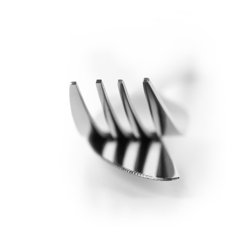 Close-up of fork and knife isolated on white background. Soft focus, shallow DOF. Focus on top of prongs. photo