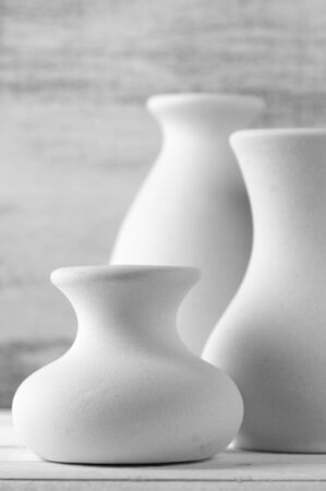 Three empty white unglazed ceramic vases on white wooden table against rustic wooden wall. Black and white image. Shallow DOF, focus on front small vase. photo