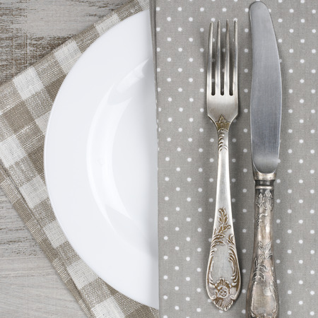 Table setting: white plate, vintage fork and knife with napkin on rustic wooden table. Top view point. photo