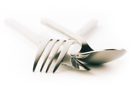 Cutlery set: fork, spoon and knife isolated on white background. Soft focus, shallow DOF. Toned image. photo