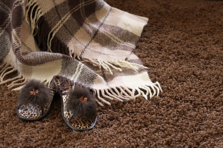 Woolen checked plaid and slippers on shaggy carpet. photo