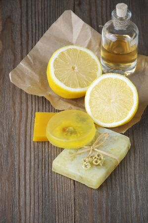 dark skin: Various natural soaps, lemon and bottle of oil on rustic wooden background. Stock Photo