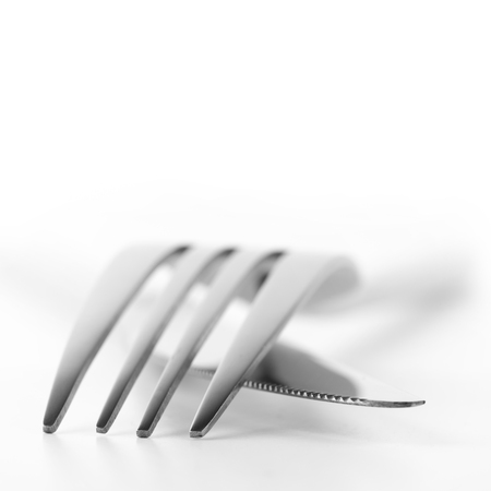 Close-up of fork and knife on white background. Soft focus, shallow DOF. photo