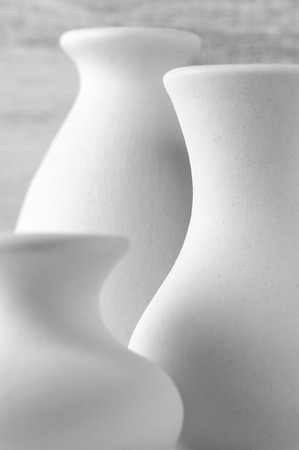 Close-up of three empty white unglazed ceramic vases against rustic wooden wall. Black and white image. Shallow DOF, focus on middle vase. photo