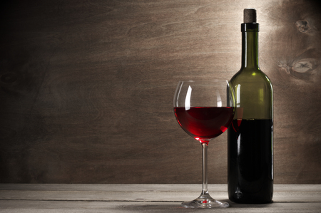 still life of wine: Glass and bottle of red wine on rustic wooden background with copy space.