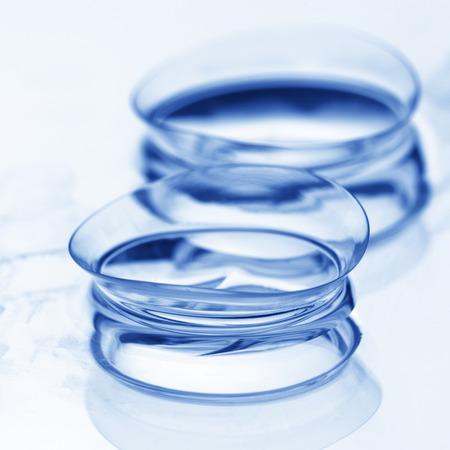 lentes de contacto: Extreme close-up de dos lentes de contacto blandas húmedas con la reflexión sobre fondo claro. DOF superficial. Imagen de tonos. Foto de archivo