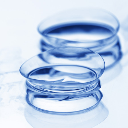 Extreme close-up of two wet soft contact lenses with reflection on light background. Shallow DOF. Toned image.