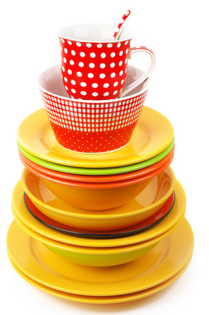 Stack of colorful ceramic dishware isolated on white background. photo