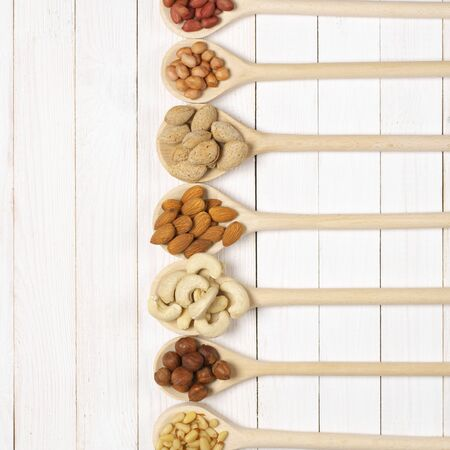 Variety of assorted nuts in spoons on white wood background with copy space. Top view point. photo