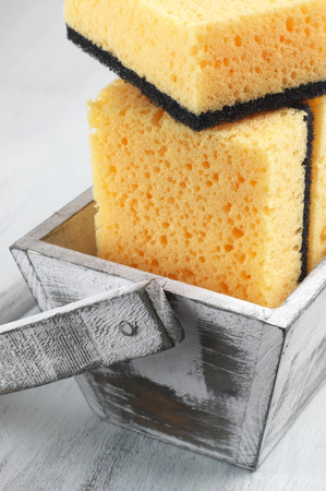 cleaning products: Cleaning sponges in rustic box on wooden background.