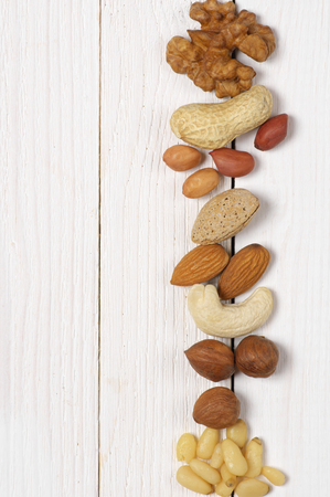 Variety of assorted nuts in row on white wood background with copy space. Top view point. photo