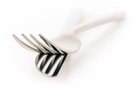 Close-up of fork and knife isolated on white background. Soft focus, shallow DOF. Toned image. photo