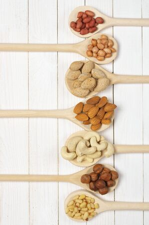 pinoli: Variety of assorted nuts in spoons on white wood background with copy space. Archivio Fotografico