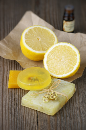 Various natural soaps, lemon and bottle of oil on rustic wooden background. photo