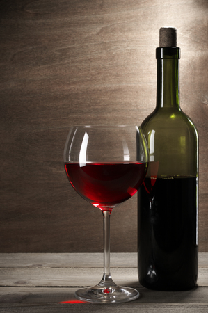 glass table: Glass and bottle of red wine on rustic wooden background.