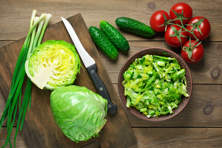 Green vegetable salad of cabbage, cucumbers and spring onion in bowl and vegetables on brown wooden table. Top view point.