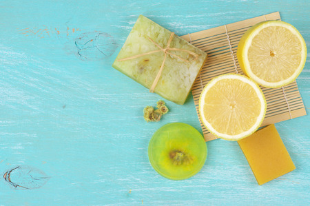 Various natural soaps and lemon on aquamarine wooden . Top view point. Stock Photo