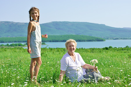 the great grandmother: Great grandmother and her great granddaughter in spring blooming meadow with chamomiles.