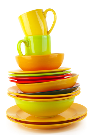 Stack of colorful ceramic dishware isolated on white background.